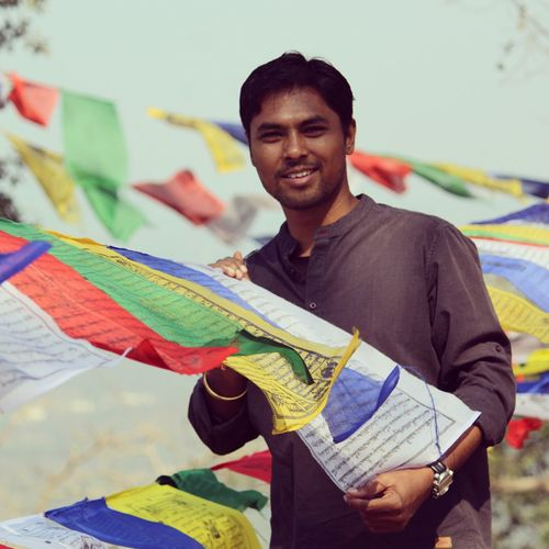 Portrait of smiling young man holding prayer flags