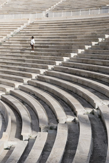 Low angle view of woman standing on steps at amphitheater
