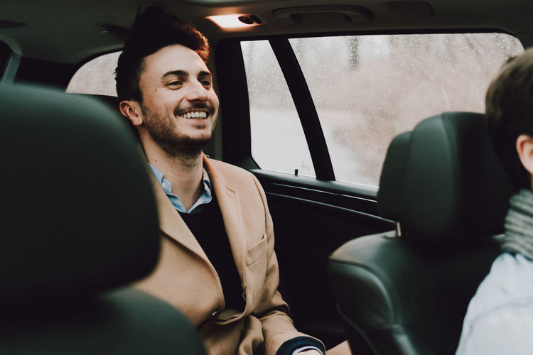 Close-up of happy businessman traveling in car