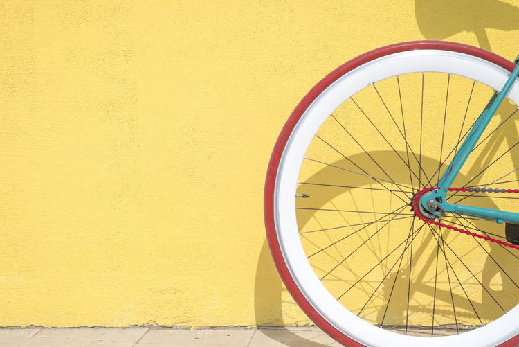 A Close-up detail of cogwheel on a vintage bicycle against a yellow wall Wheel Yellow Transportation Bicycle Mode Of Transportation No People Wall - Building Feature Day Tire Land Vehicle Outdoors Built Structure Architecture Spoke Close-up Copy Space Wall Stationary Building Exterior Sunlight Fixie Fixed Bike Vintage Wheel Wall Leaning Retro Styled Old Vehicle Transportation Ecological Sustainable Resources
