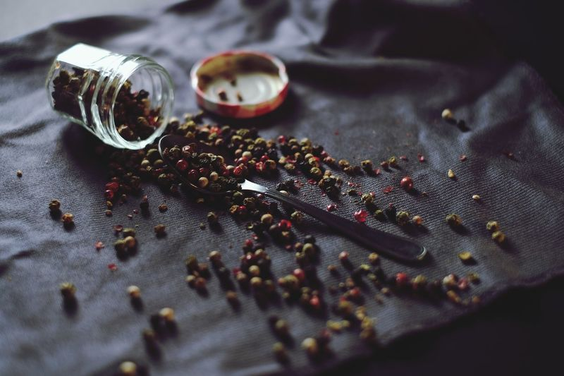 Close-up of black peppercorns spilling on fabric