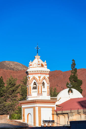 Spire of the cathedral in Tupiza, Bolivia with red hills in the background Andean Andes Beauty Bolivia Canyon Cathedral Church Color Colorful Country Countryside Desert Formation Full Grass Hills Landscape Mountains Nature South America Spire  Tradition Travel TUPIZA Valley
