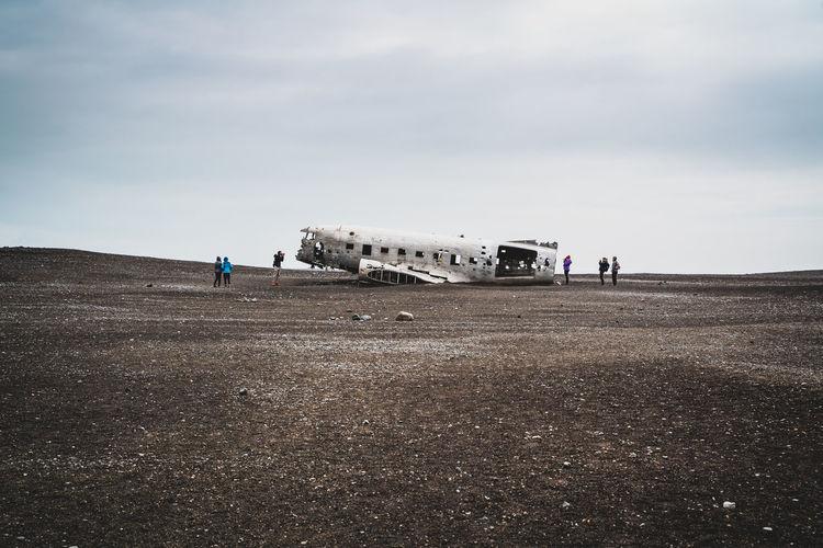 People on airport runway against sky