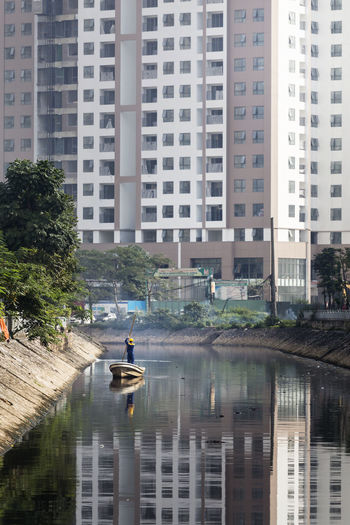 People in river against buildings in city