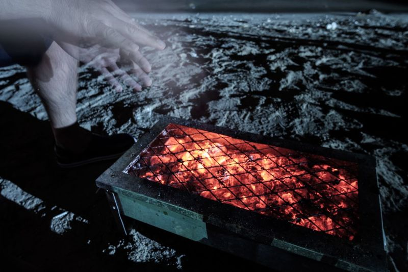 Getting Warm Barbecue Burning Burning Close-up Coal Cold Temperature Fire Grill Heat - Temperature Hot Human Body Part Human Hand Illuminated Leisure Men Night Night Photography One Person People Real People Winter