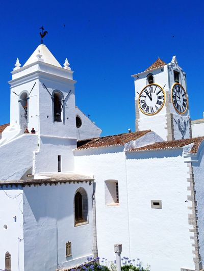 Low angle view of church against clear blue sky during sunny day