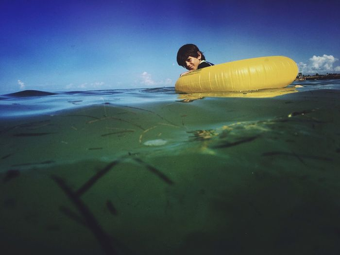 Portrait Of Boy With Inflatable Ring At Sea Against Sky