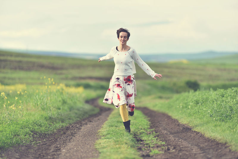 Woman in white skirt running on a countryside road. Freedom concept Alone Freedom Happiness Happy Happy People Nature Road Running Woman Countryside Countryside Road Dirty Road Energy Escape From The City Female Girl Instagram Filter Joy Joyful Moments Landscape Meadow Outdoors Positivity Skirt Toned Image Woman