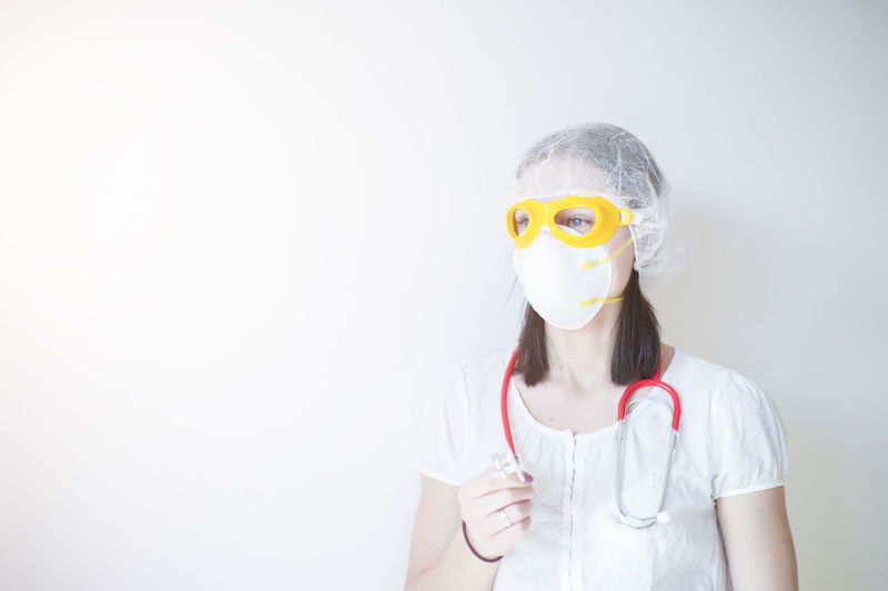Portrait of teenage girl wearing mask against white background