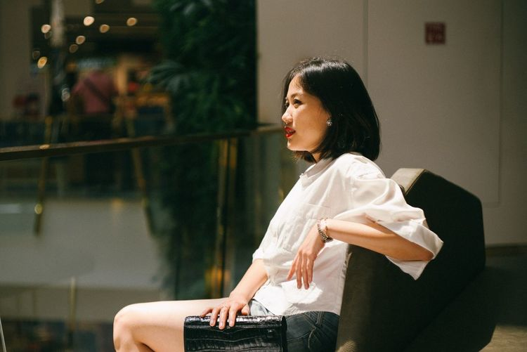 Side View Of Beautiful Woman Sitting In Shopping Mall