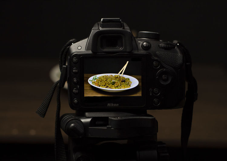 Close-up of camera on table against black background