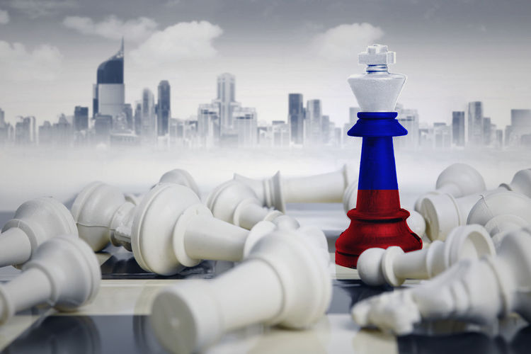 Digital composite image of chess pieces with flag against buildings in city