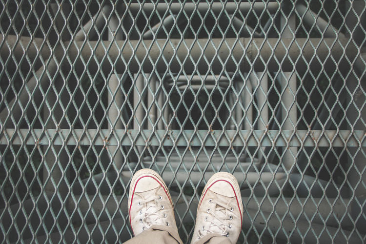 Low section of man standing on chainlink fence