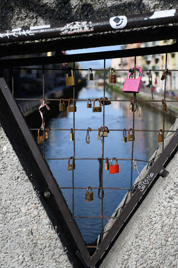 Padlocks hanging on railing by canal