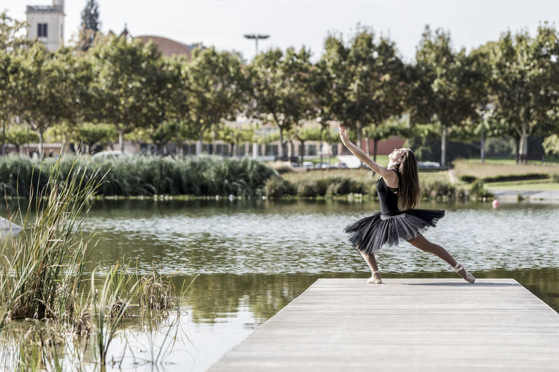 Woman Ballet Dancing On Pier Over Lake Against Sky