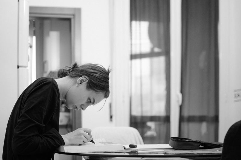 Side view of young woman studying at table