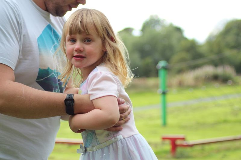 Midsection Of Man Holding Cute Daughter On Field