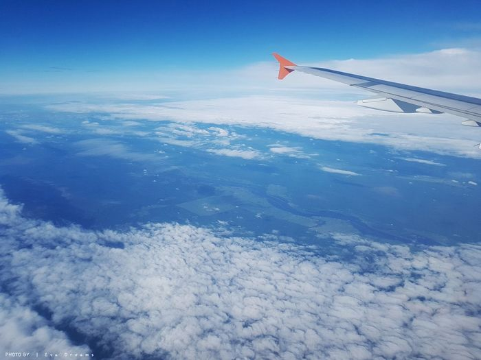 Aerial view of airplane flying over clouds against blue sky