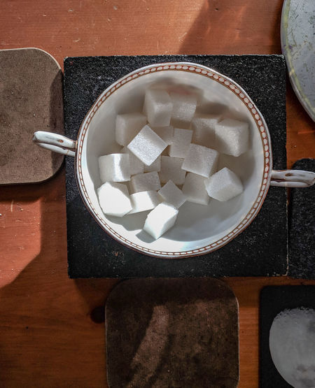 sugar cubes on sunlit table Old-fashioned Sunlight Table Flat Lay Wooden Rustic Shabby Drink Table Sugar Cube Sugar Directly Above High Angle View Close-up Sweet Food Food And Drink Saucer Coffee Cup