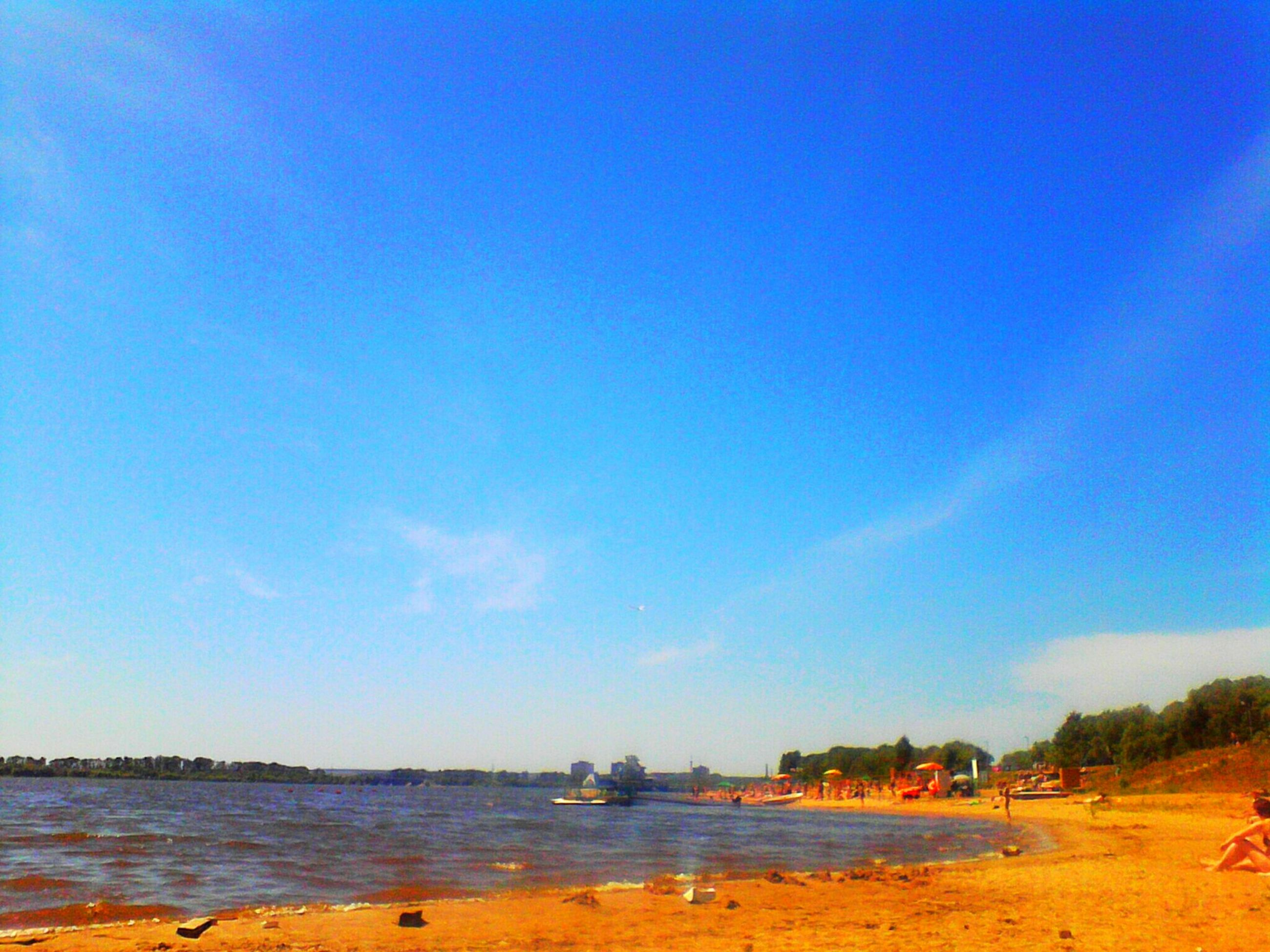 beach, water, blue, sand, sea, tranquil scene, tranquility, shore, scenics, beauty in nature, sky, nature, copy space, idyllic, incidental people, clear sky, horizon over water, coastline, non-urban scene, day