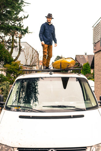 Portrait of young man standing on car roof