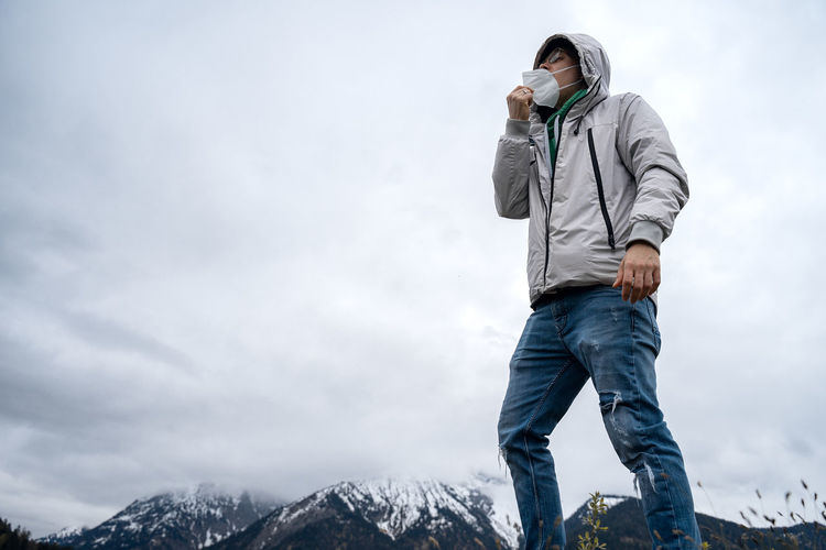 Traveler stands on the top of the mountain and takes off the medinic ffp2 face mask to take a breath