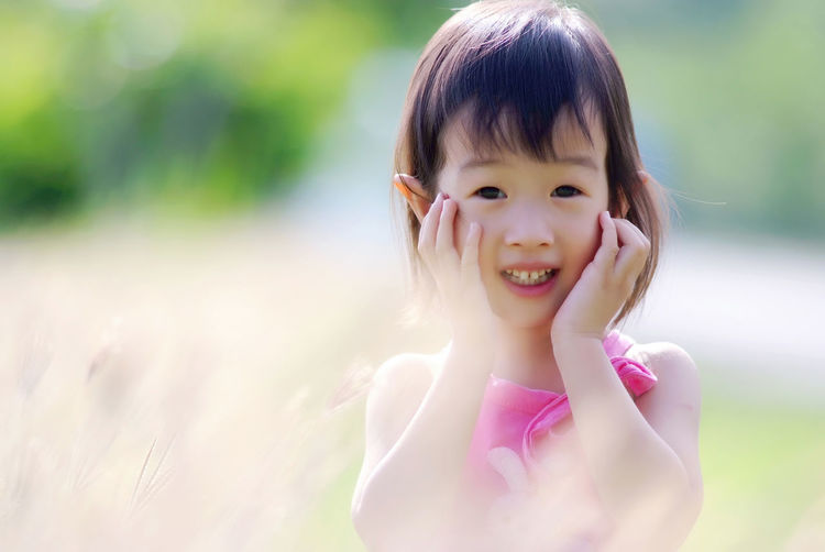 Portrait of happy girl with hands on cheeks standing outdoors