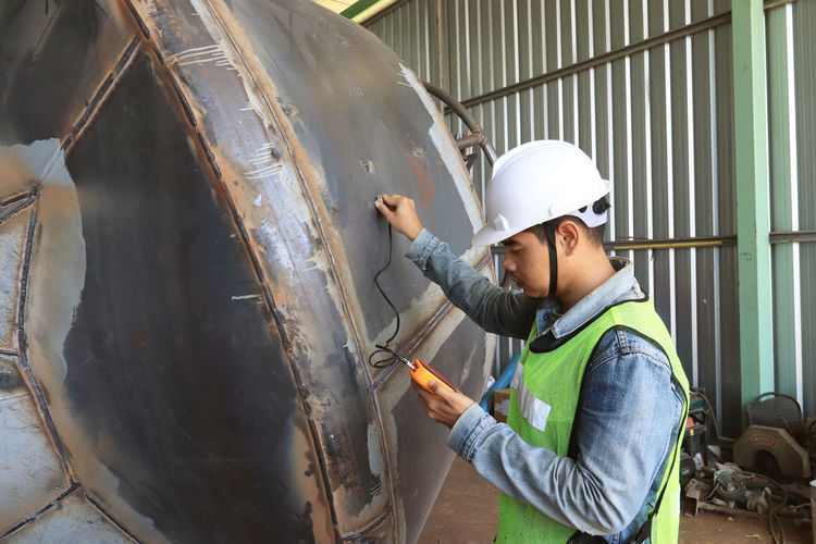 Mechanic engineer in factory checking quality of metals