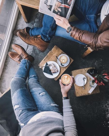 Low Section Of Male Friends Having Coffee In Cafe