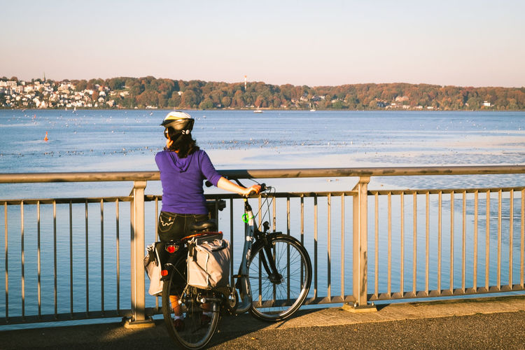 Woman with bicycle on railing against clear sky