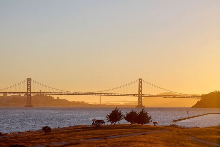 San franciscooakland bay bridge over sea against sky during sunset