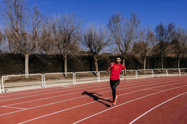 Full length of athlete running on sports track