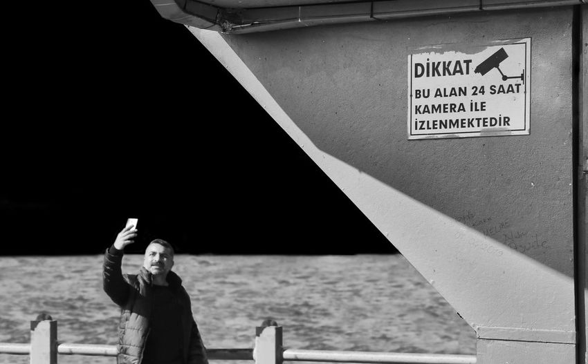 Man using mobile phone while standing by sea against sky