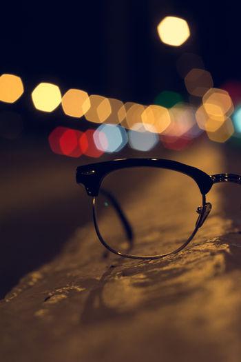 Surface Level Image Of Eyeglasses Against Illuminated Lights At Night