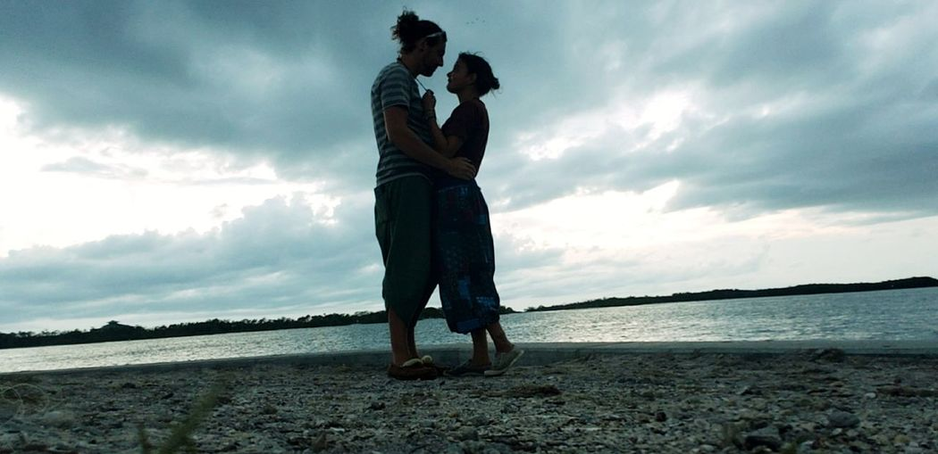 Couple standing at beach against sky