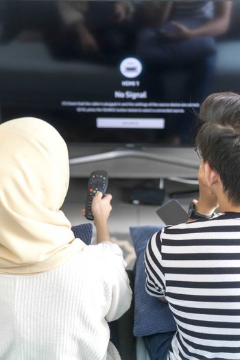 Young Malay Couple at the Sofa watching tv together Rear View Real People Men Adult Lifestyles Two People People Technology Leisure Activity Women Casual Clothing Indoors  Togetherness Headshot Males  Communication Child Boys Photography Themes Focus On Foreground