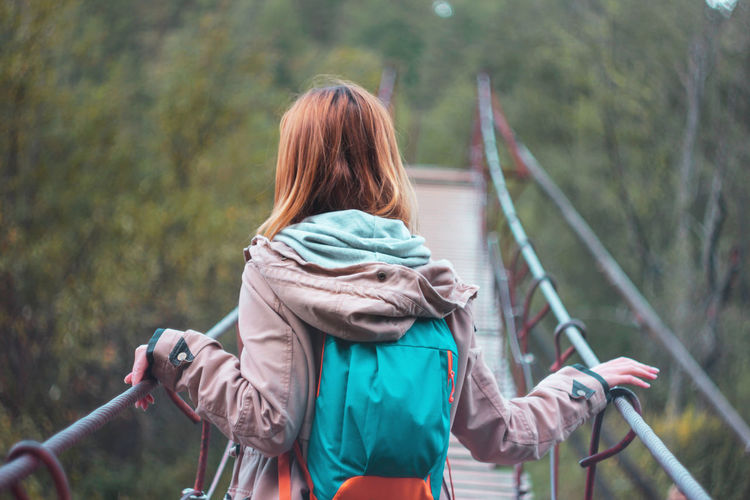 Rear view of woman standing on footbridge