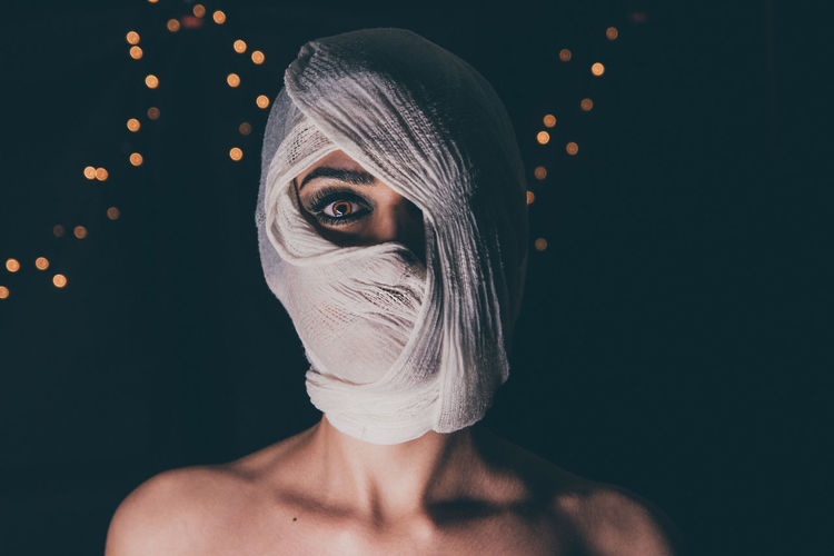 Close-Up Portrait Of Woman Face Covered With Fabric At Night