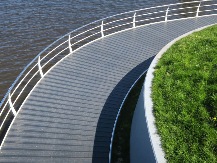 curving sidewalk bridge Architecture Built Structure Connection Curve Day Environment Flowing Water Grass High Angle View Nature No People Outdoors Plant Railing Sidewalk Bridge Steel Sunlight Water Wooden