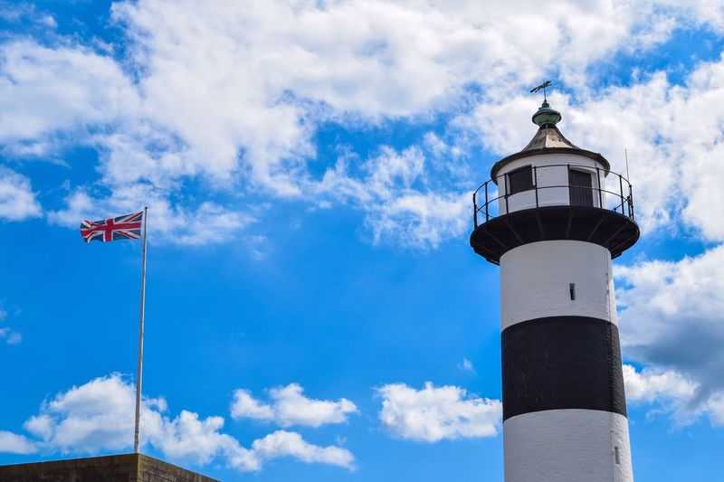 Low Angle View Of Lighthouse Against Blue Sky And Clouds