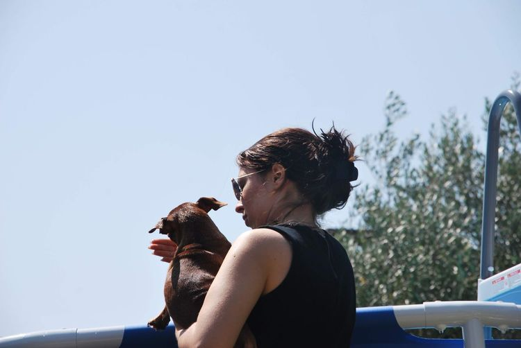 Low angle view of woman holding dog against clear sky