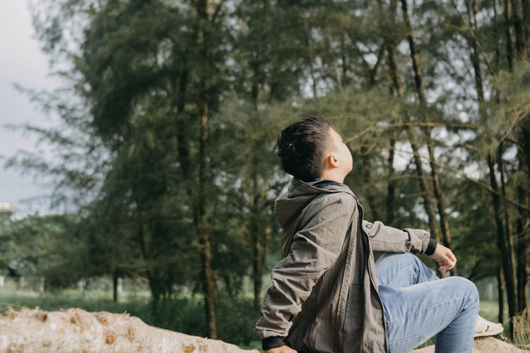 Side view of young man sitting in forest
