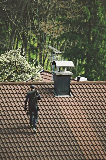 High angle view of chimney sweep walking on roof