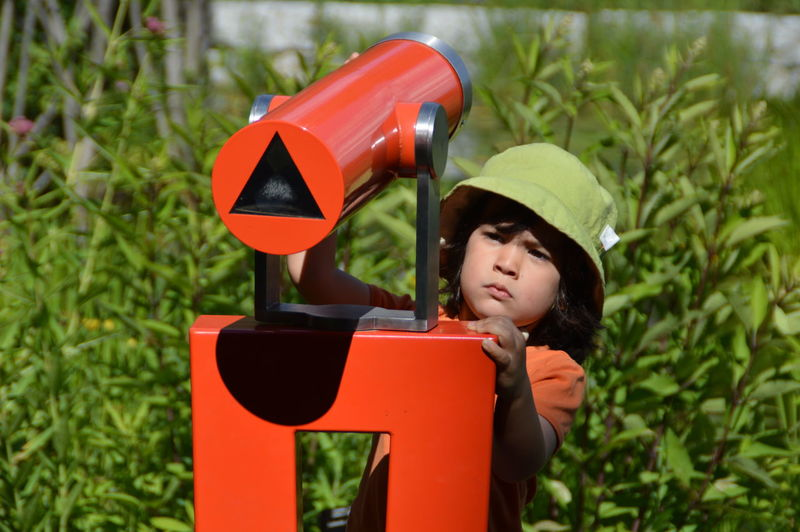 Boy using red hand-held telescope against plants on sunny day