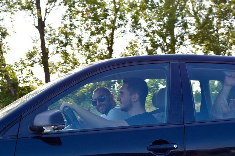 Portrait of man sitting with friend in car seen through window