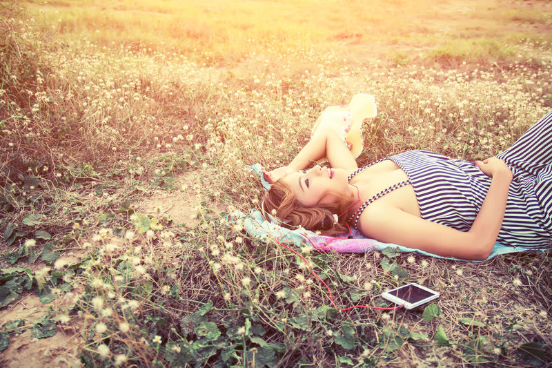 Casual Clothing Child Childhood Day Field Full Length Grass Innocence Land Leisure Activity Lens Flare Lifestyles Lying Down Nature One Person Outdoors Plant Real People Relaxation Sunlight Women