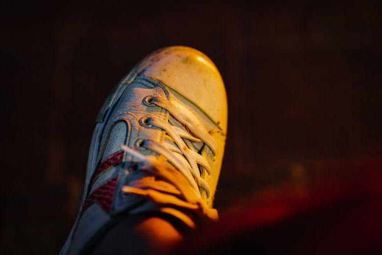Low section of person wearing shoe at night