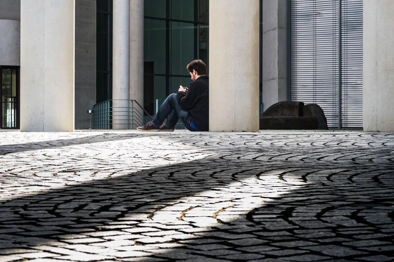 Full length of woman sitting on sidewalk in city