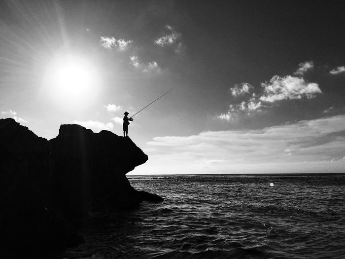 Silhouette person on rock by sea against sky
