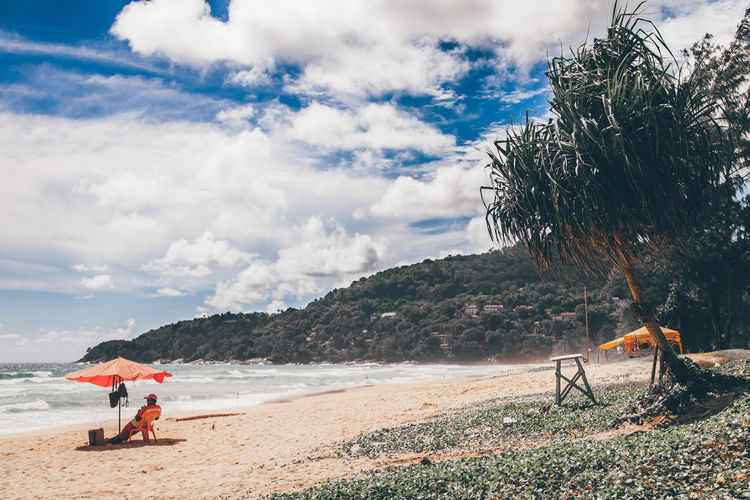 Lifeguard on duty EyeEmNewHere Landscape Newhere Island Tree Spraying Water Beach Full Length Sand Men Sky Cloud - Sky Lifeguard Hut